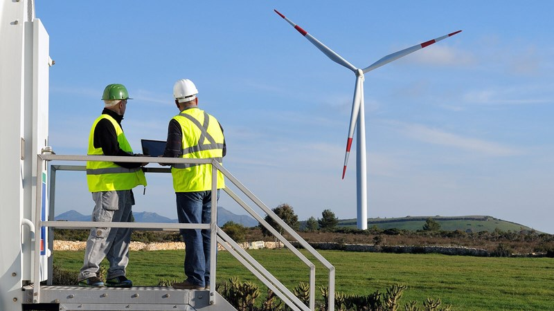 Two engineers in high viz vests study a wind turbine in the distance.