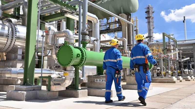 Two engineers wearing hi-visibility overalls, walk alongside the external pipes of a large fuel plant. Fotolia #129126524