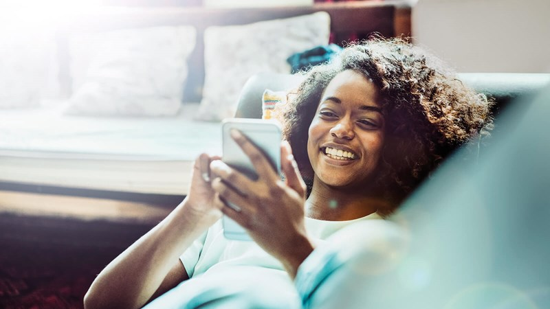 Smiling woman reclining on couch looks at her phone